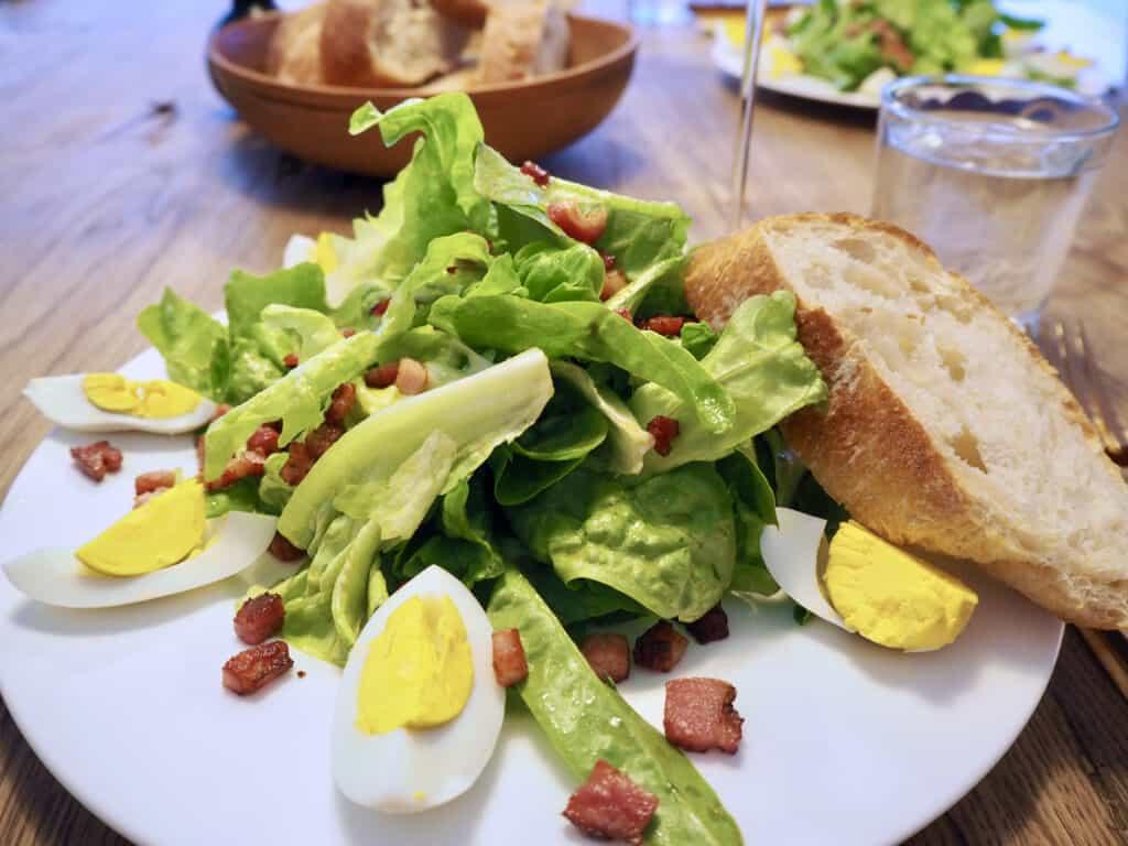 Grüner Salat mit Ei und Speck
